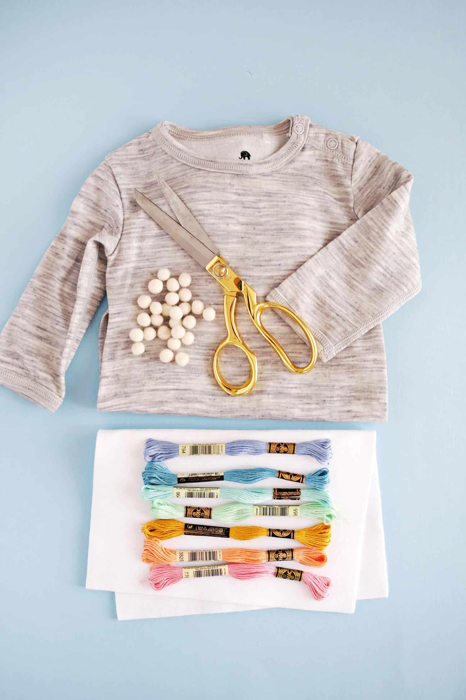 8e4fd166a -embroidery thread in 7 rainbow colors -white wool felt sheet -washi tape  -needle, thread, and fabric scissors –plain colored romper -fabric glue